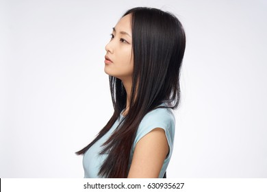 Asian woman in profile, light background