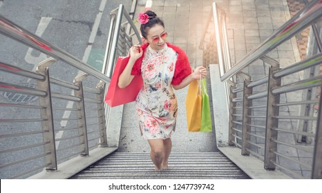 Asian woman put sumglas in traditional chinese long dress, cheongsam, black hair, carrying paper shopping bags a customer for Chinese New Year festival, celebration time During the walk up the stairs.