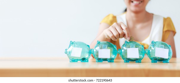 Asian woman putting money coin in to clear piggy bank with white blank paper metaphor saving money financial for difference budget ratio for web banner and header design with copy space
