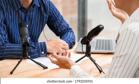 Im Radio einer asiatischen Frau wird die Geste zu Mikrofon aufgenommen, während man einen männlichen Gast in einem Studio interviewt, während man gemeinsam Podcast für eine Online-Show im Studio aufnimmt.