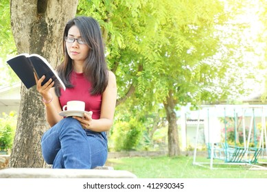 Asian woman reading book and holding coffee under the tree in autumn park ,nature and education concept, selective focus