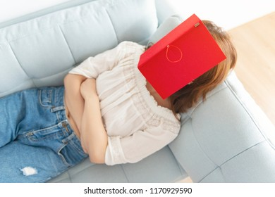 Asian woman reading a book sleeping at home