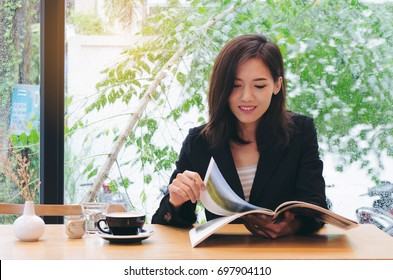 Asian woman reading magazine in coffee shop.business concept.