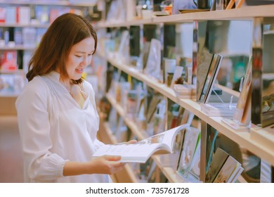 Asian woman reading recipe book before buying at store
