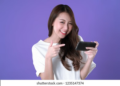 Asian woman recommended to play mobile game on smartphone, white t-shirt clothing, purple background