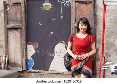 Asian Woman in red dress ,Street photo at Yaowarat Road in Bangkok, Thailand.