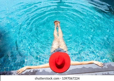 Asian woman with red hat relax on swimming pool. Summer in Thailand location.