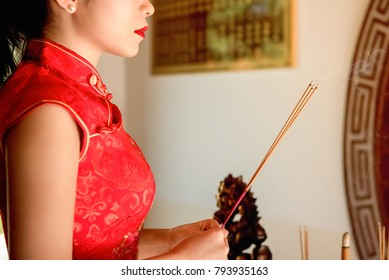 Asian woman in red qipao dress praying with incense sticks during Chinese or Lunar new year