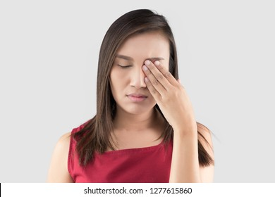 Asian woman in the red shirt has pain in the eye on a gray background, Closing Eyes With Hand, itching, The tired exhausted stressed female suffering from strong eye pain