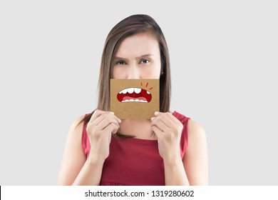 Asian woman in the red shirt holding a brown paper with the broken tooth cartoon picture of his mouth against the gray background, Decayed tooth, The concept with healthcare gums and teeth