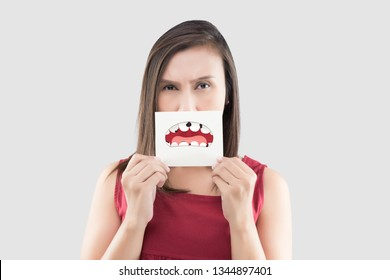 Asian woman in the red shirt holding a brown paper white the broken tooth cartoon picture of his mouth against the gray background, Decayed tooth, The concept with healthcare gums and teeth