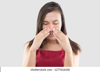 Asian woman in red wear feeling unwell because of sinus against a gray background. People caught a cold and fever. The concept of healthcare and allergy
