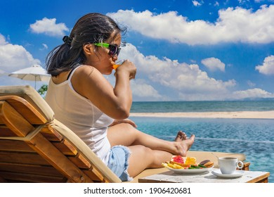 Asian woman relax and drink orange juice in the beach