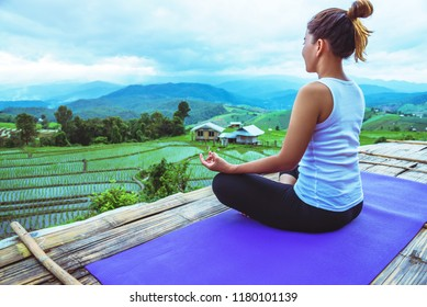 Asian woman relax in the holiday. Play if yoga. On the balcony landscape Natural Field