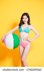 asian woman is relaxed and carefree and ready to travel wearing bikini swimsuit with beach ball