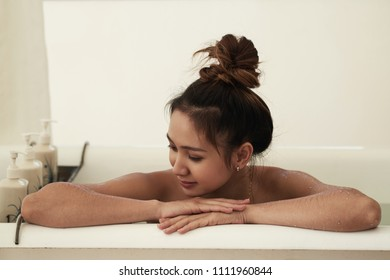 Asian woman relaxing in bath at home