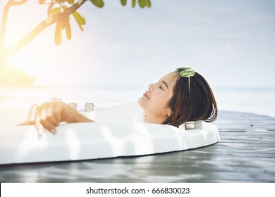 asian woman relaxing in a bathtub at hotel in koh chang