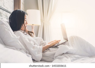 asian woman relaxing in the hotel room and working on labtop, copy space
