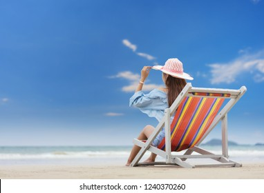 Asian woman relaxing on a beach chair and raising their arms to catch a hat.summer vacation concept.pattaya beach thailand