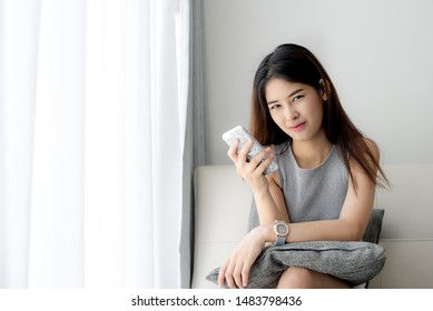 Asian woman relaxing on sofa and using smart phone at home, lifestyle concept.