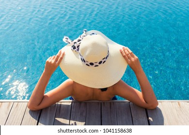 Asian woman relaxing in swimming pool with sunbathe.