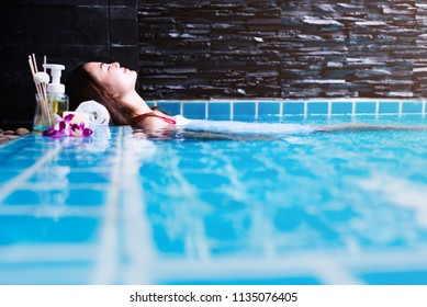 Asian woman relaxing in swimming pool at spa resort.relaxing concept.