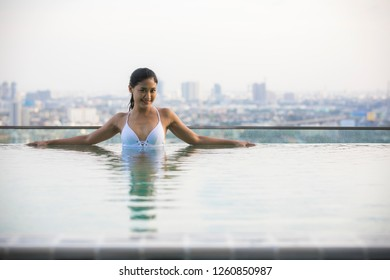 Asian woman relaxing in swimming pool on rooftop with Smiling and happy emotion