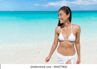 Asian woman relaxing walking on beach in white bikini and cover-up wrap swimwear in turquoise ocean background at Caribbean tropical destination.