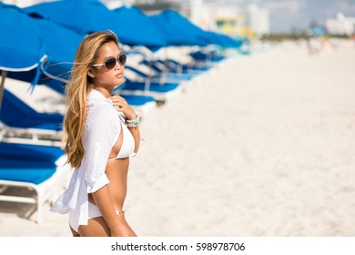 Asian woman relaxing walking on beach in white bikini and cover-up wrap swimwear at tropical vacation
