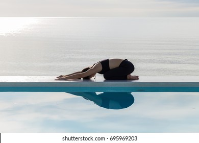 Asian woman relaxing in yoga Child's Pose on the pool above the beach with beautiful sea,Feeling so comfortable and relax in holiday