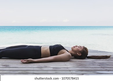 Asian woman relaxing in yoga Savasana pose to meditation warm up her muscle on beach in Maldives with seaside,Feeling so comfortable and relax in holiday