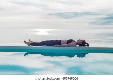 Asian woman relaxing in yoga Savasana pose on the pool above the beach with beautiful sea,Feeling so comfortable and relax in holiday