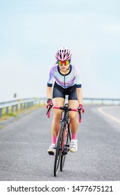 asian woman riding bicycle on asphalt road
