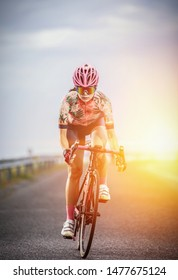asian woman riding bicycle on asphalt road against sunrise