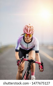 asian woman riding bicycle on race against sunrise