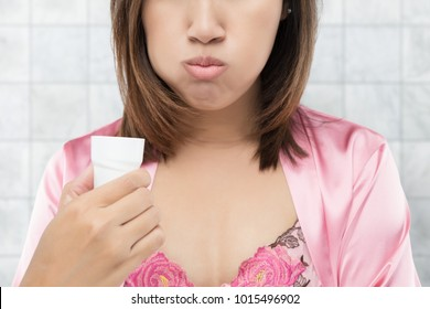 Asian Woman rinsing and gargling while using mouthwash from a glass, During daily oral hygiene routine, Female in a pink silk robe, Dental Healthcare Concepts