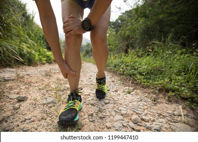 Asian woman runner hold her sports injured leg on rocky trail