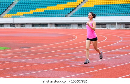 asian woman runner running in the athletics field