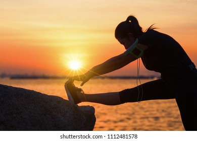 Asian woman runner stretching legs before run outdoor workout in the park at sunset. exercise,healthy,relaxing concept.