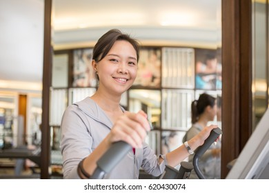 Asian woman running inside fitness room.