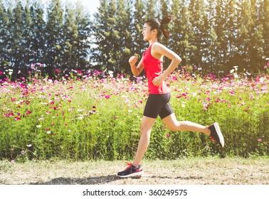 Asian woman running on beautiful flower garden. Her morning exercise