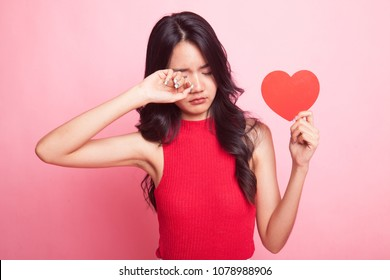 Asian woman sad and cry with red heart on pink background