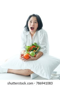 Asian woman with salad vegetables on white background