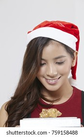 asian woman with santa hat holding present box with ribbon