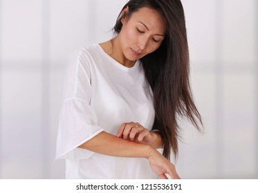 Asian Woman Scratching an itch on white background . Sensitive Skin, Food allergy symptoms, Irritation