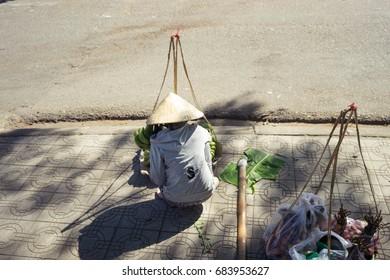 asian woman selling fruit on street