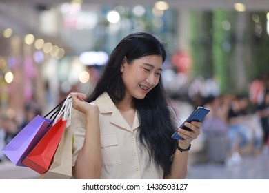 Asian woman with shopping bag in the shopping mall happy and smile face with sale time discount on front of shop
