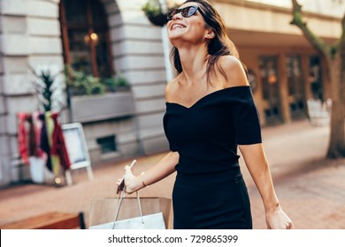 Asian woman with shopping bags enjoying on city street. Female walking outdoors with shopping bags and smiling.