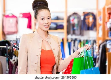 Asian Woman shopping in boutique or fashion store