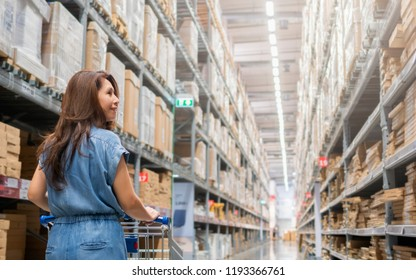 Asian woman with shopping cart choosing new furniture and standing in Warehouse aisle.